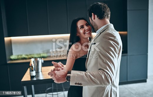 Stylish couple dancing on modern kitchen together. Handsome bearded man in suit and attractive woman in black dress at home.