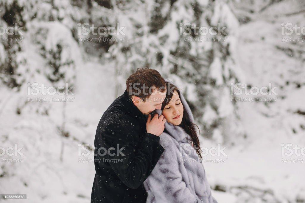 ed94fa1383 Couple élégant globale dans les montagnes d'hiver enneigé. Heureux homme  romantique et femme