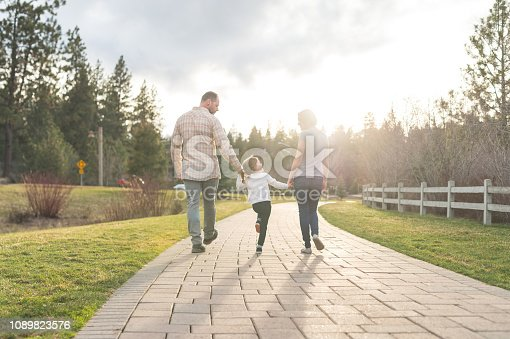 Mom and dad walk hand in hand with their young daughter on a boardwalk. The sun is setting ahead of them and the shot is from behind them.. Both are looking down at their girl affectionately and smiling.