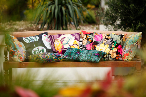 Stylish cushions on wooden seat placed in garden