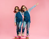 Stylish cute girls with skateboard and wearing fashion clothes on pink background. Happy children with skateboard enjoying together.