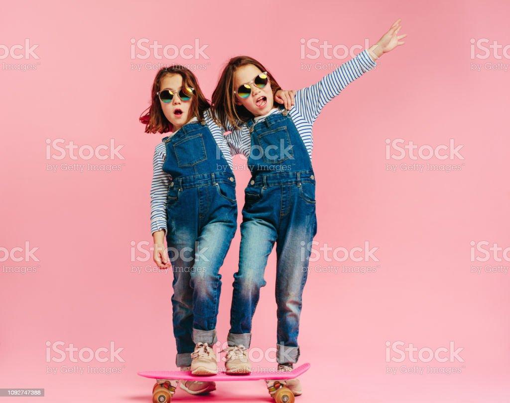 Stylish cute girls with skateboard stock photo
