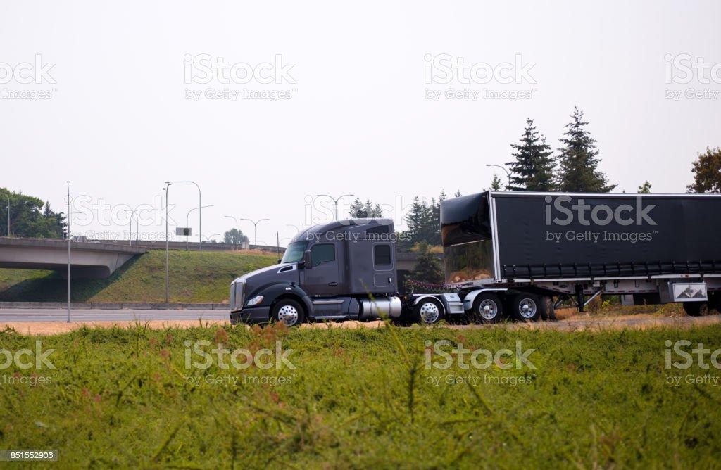 Stylish dark big rig modern semi truck with a black semi trailer run on the highway exit stock photo