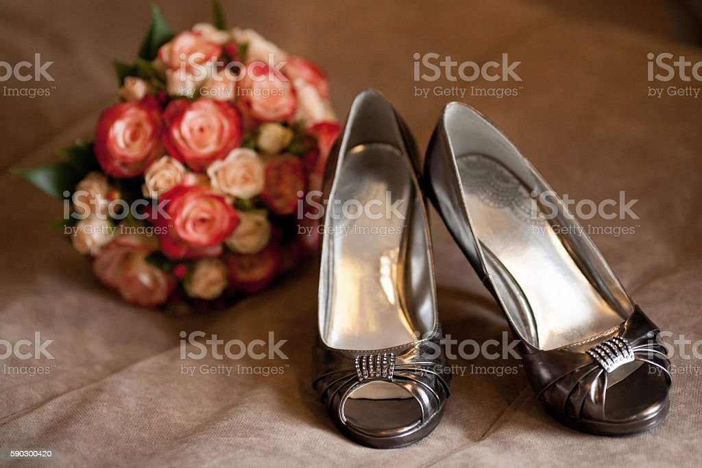 Stylish dark bridal wedding shoes with rose bouquet. Marriage concept royaltyfri bildbanksbilder