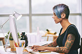 Side view of alternative style woman working on computer in office