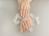Stylish fashionable women pink manicure with feathers