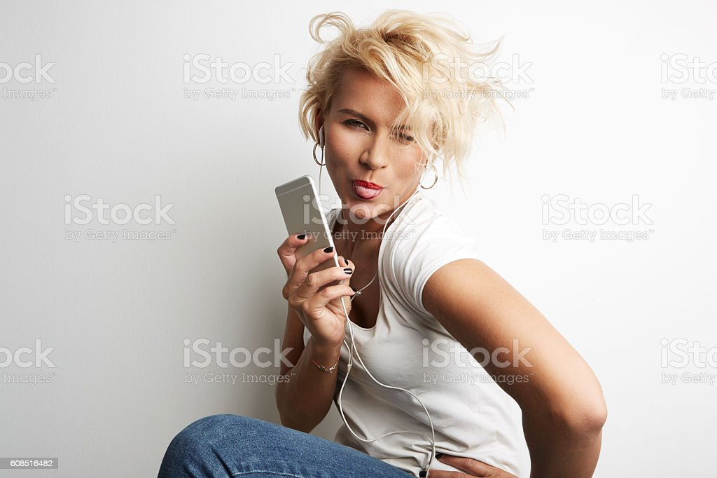 Stylish Female Making Selfie Smartphone While Standing Against White Background стоковое фото