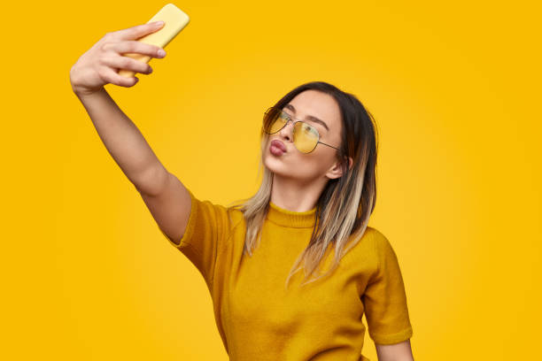 Stylish female pouting lips and taking selfie Young woman in trendy outfit pouting lips and using smartphone to take selfie while standing against yellow background puckering stock pictures, royalty-free photos & images