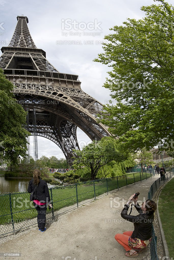 Stylish female tourist takes photograph of Eiffel Tower in Paris royalty-free stock photo