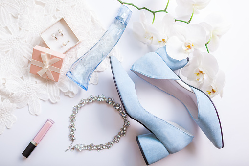 istock Stylish female wedding clothes, blue shoes and accessories with flowers. Morning of bride 1155609874