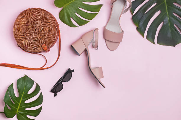 Stylish feminine summer accessories and monstera leaves on the pastel pink background, stock photo
