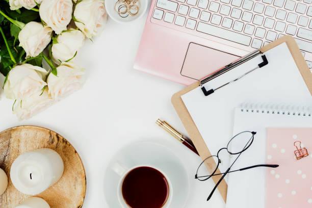 stilvolle flatlay frame anordnung mit rosa laptop, tee, rosen, gläser und sonstiges zubehör auf weiß. feminine business-modell - rosen tee stock-fotos und bilder