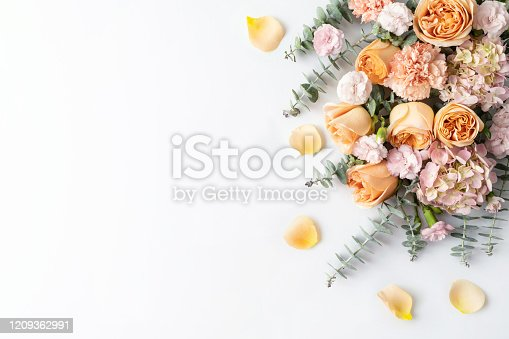 A flower arrangement of peach roses, pink hydrangeas, purple carnations and eucalyptus leaves. Celebrate your wedding, birthday, anniversary, valentine's day, baby shower or mothers day with this stylish flora display.
