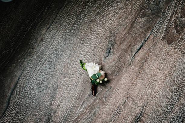 stilvolle blumenboutonniere für männer bräutigam, hochzeitsaccessoires auf rustikalem holzhintergrund. handgemachte, traditionelle idee für komposition. urlaubskonzept. flat-lay. top view. - brautstrauß aus holz stock-fotos und bilder