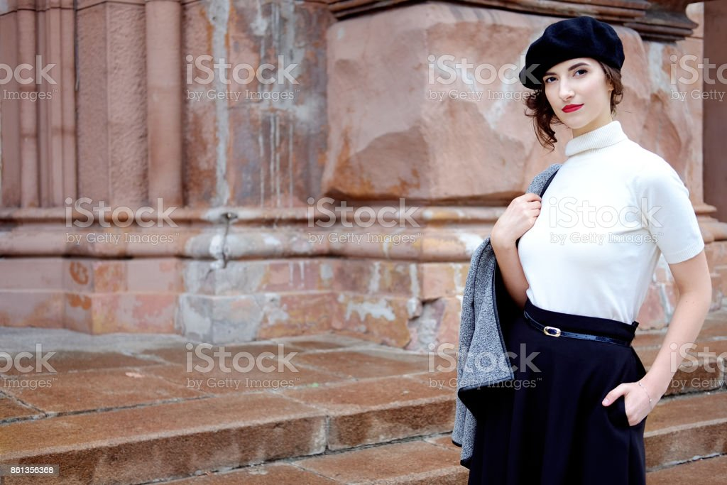 Stylish french girl in beret walking outdoors in autumn inthe old city stock photo