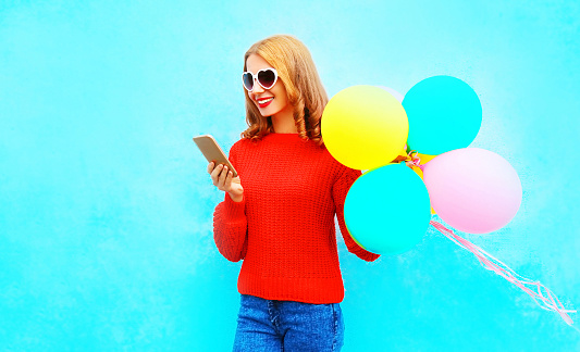 istock Stylish fummy girl is using smartphone with an air balloons on blue background 975191422