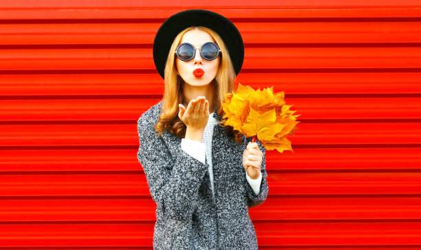 Stilvolle lustige Herbst Frau sendet einen Luft-Kuss mit gelben Ahornblätter, trägt einen Mantel auf rotem Grund – Foto