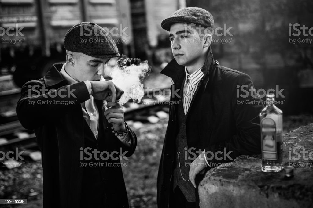 stylish gangsters smoking in tweed outfit posing on background of railway carriage. england in 1920s theme. fashionable look of brutal confident man. atmospheric moments stock photo