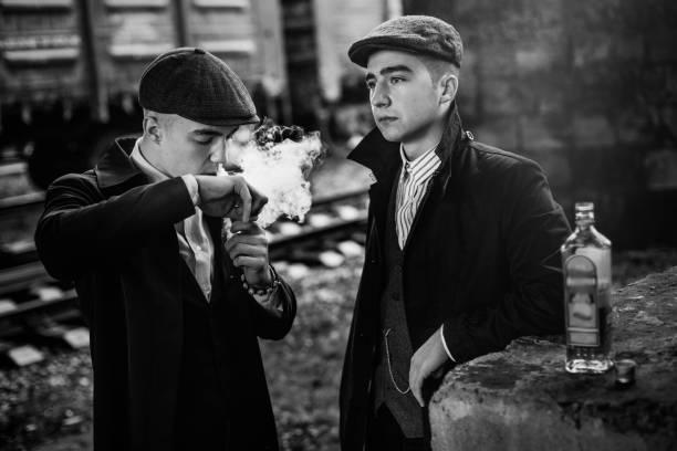 stilvolle gangster rauchen in tweed outfit posiert auf hintergrund von eisenbahnwagen. england in den 1920er jahren thema. modischen look des brutalen zuversichtlich menschen. stimmungsvolle momente - scheuklappe stock-fotos und bilder