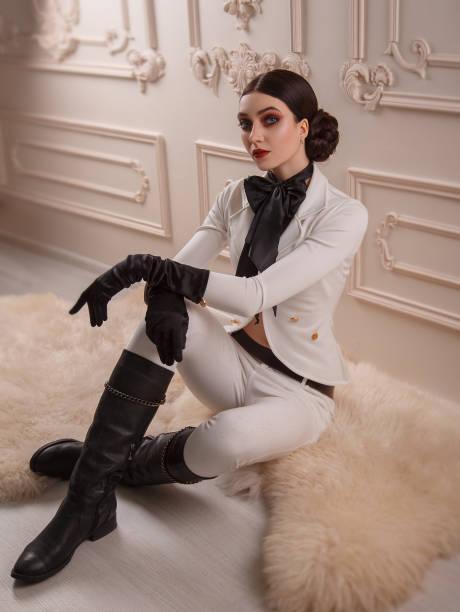 stilvoll, mädchenjäger, in einem weißen vintage-kostüm pferdeschwanz mit hohen lederstiefeln. eine dame posiert vor dem hintergrund eines klassischen interieurs. make-up smokey augen, strenge, kreative frisur - königin kopfteil stock-fotos und bilder