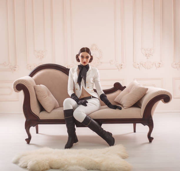 stilvoll, mädchenjäger, in einem weißen vintage-kostüm pferdeschwanz mit hohen lederstiefeln. eine dame posiert vor dem hintergrund eines klassischen interieurs. make-up smokey augen, strenge, kreative frisur. - königin kopfteil stock-fotos und bilder