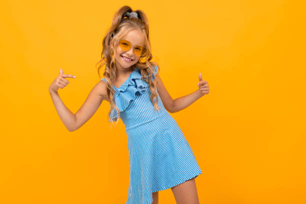 stylish girl in a dress in bright glasses on an orange background stock photo