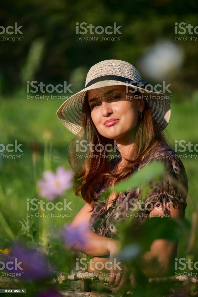 Stylish girl in a picturesque summer garden stock photo