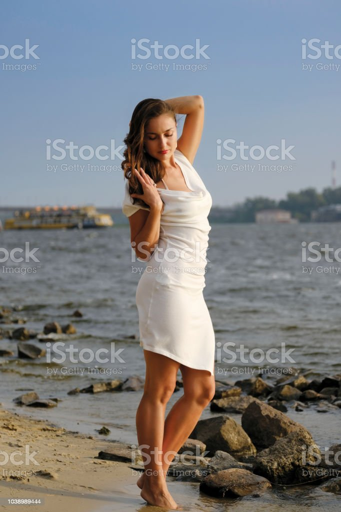 Stylish girl in a vintage dress on the beach stock photo