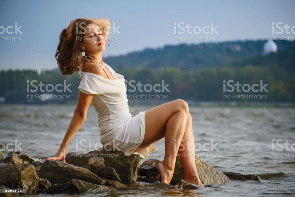 Stylish girl in a vintage dress on the shore stock photo