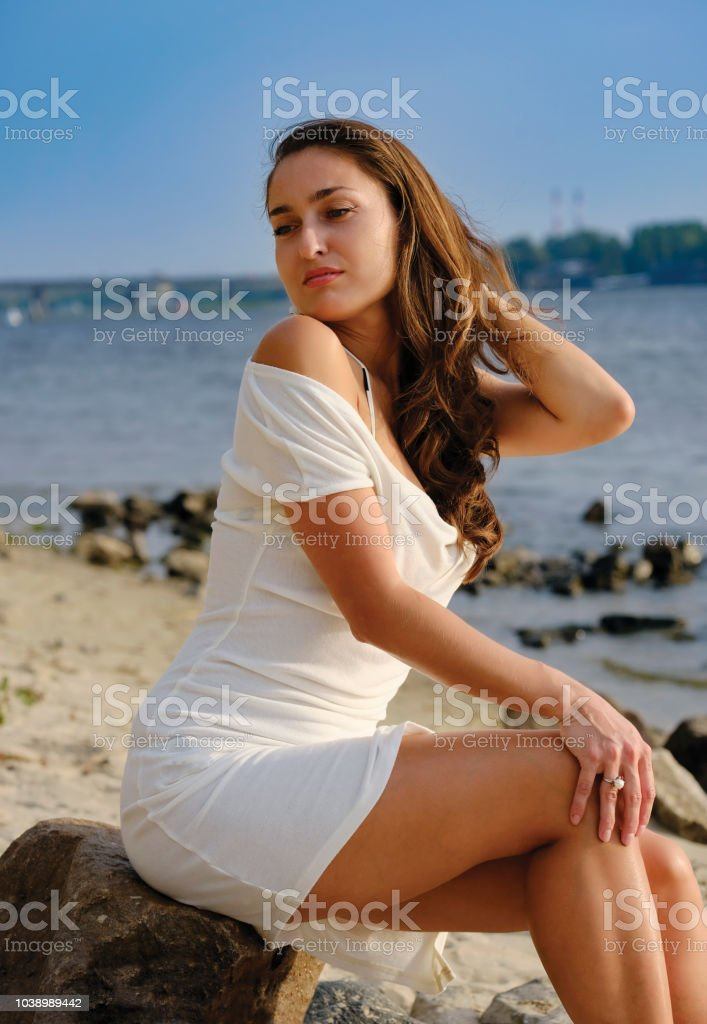 Stylish girl in a vintage dress on the shore sits on a rock stock photo