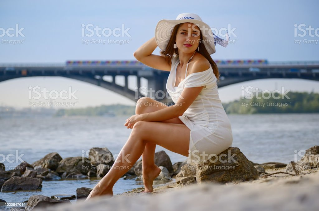 Stylish girl in a vintage hat on the shore stock photo