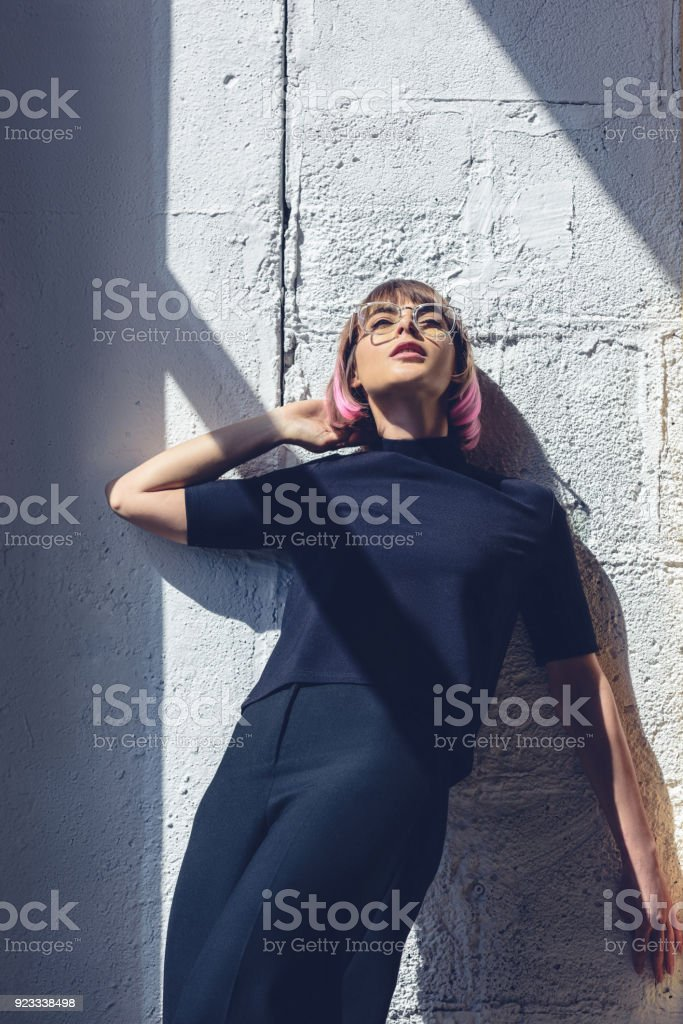 97f02c773 Stylish Girl In Black Clothes Leaning On Wall And Looking Up Stock ...
