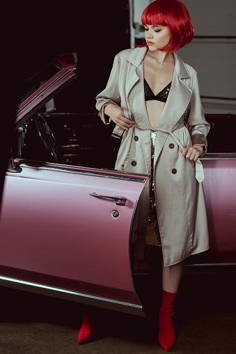 Stylish Girl In Bra And Trench Coat Standing Near Retro Car