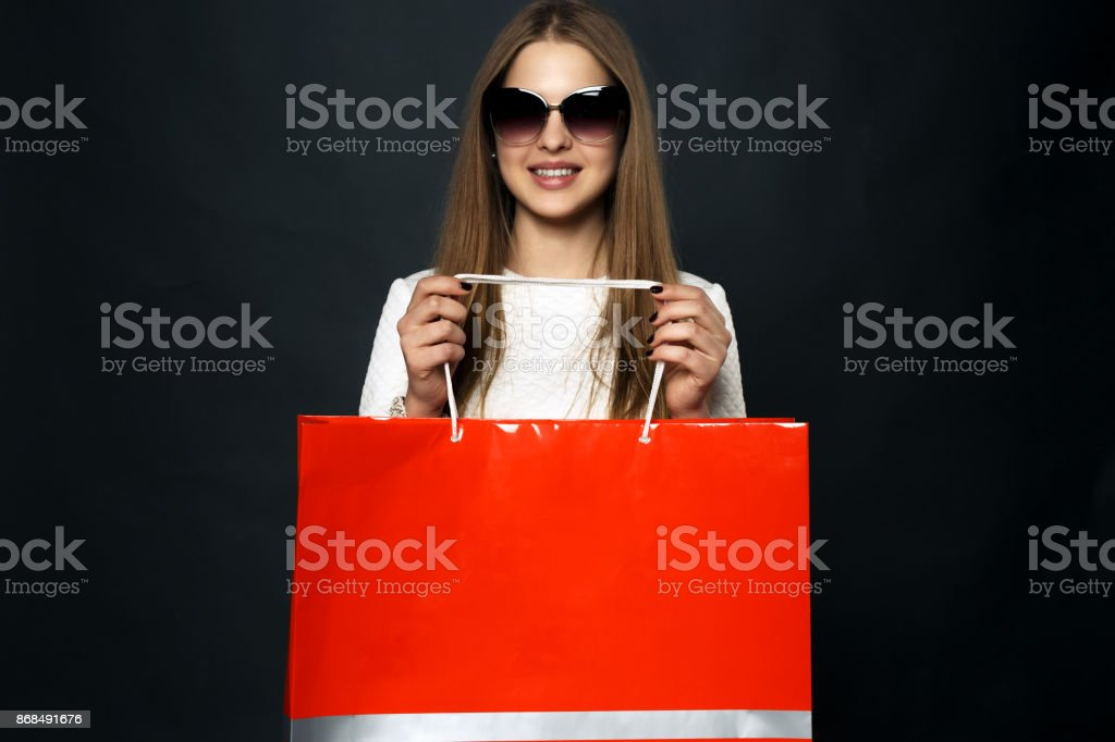 Stylish girl in sunglasses and a white dress, holds red package for shopping, isolated against a dark background. Template. Mock-up stock photo