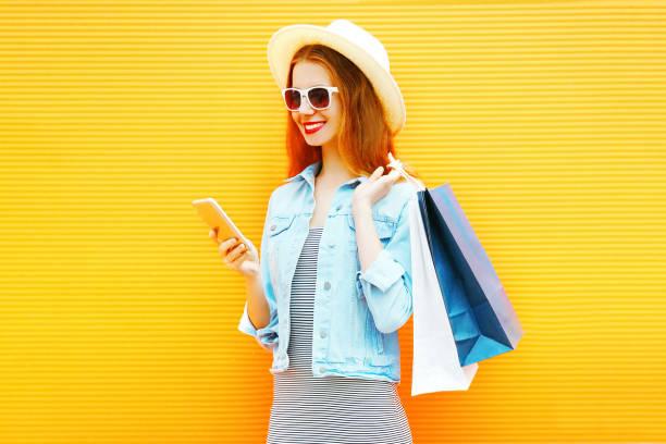 stilvolles mädchen nutzt das smartphone in der stadt auf orangem hintergrund - dresses online shop stock-fotos und bilder