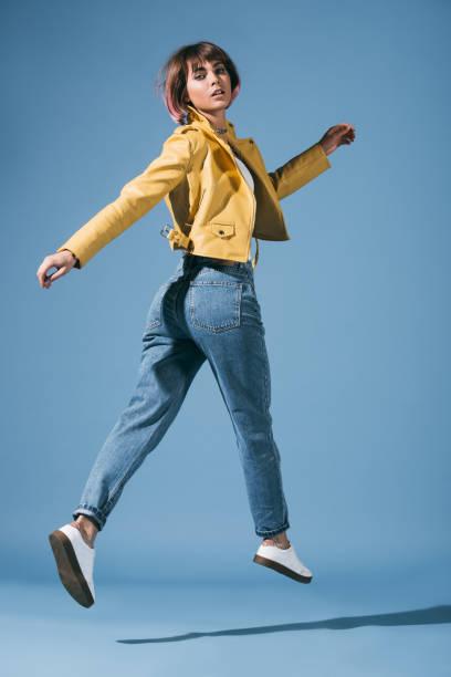 時尚的女孩跳, 看著藍色的相機 - 牛仔褲 個照片及圖片檔