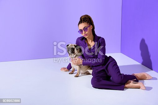 istock stylish girl posing in trendy purple suit with pug dog, ultra violet trend 928952886