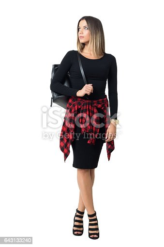 Stylish girl in high heels carrying bag looking back over the shoulder. Full body length isolated over white studio background.