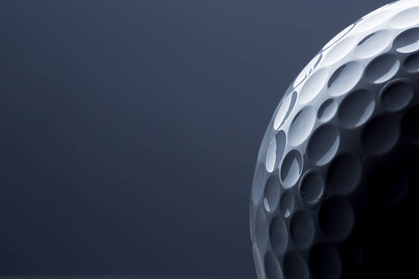 Stylish golf ball isolated on empty dark blue background. stock photo