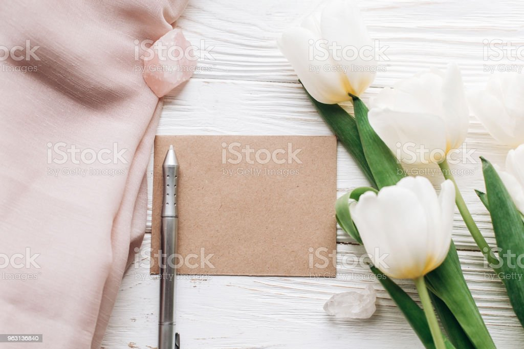 stylish greeting card template with tulips and crystals and pen. boho wedding invitation on white wooden rustic background. flat lay. photo workshop. space for text. stock photo