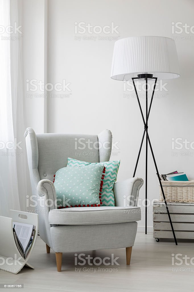 Stylish grey armchair and a floor standing lamp stock photo