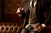 Stylish groom holds in his hand a glass of whiskey