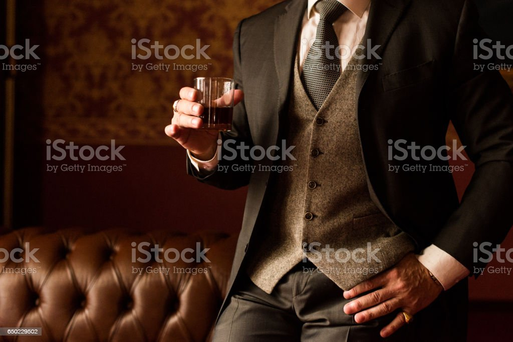Stylish groom holds in his hand a glass of whiskey – zdjęcie