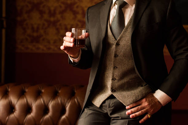 stylish groom holds in his hand a glass of whiskey - costume photos et images de collection