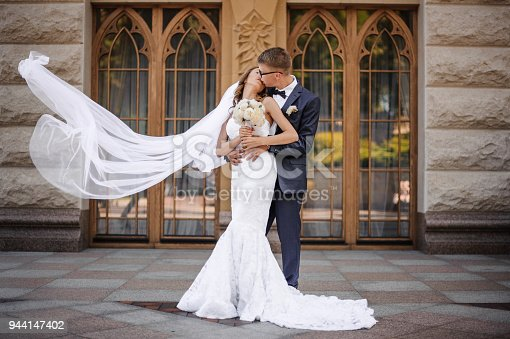 istock stylish groomis going to kiss the charming bride on the background of wooden doors 944147402