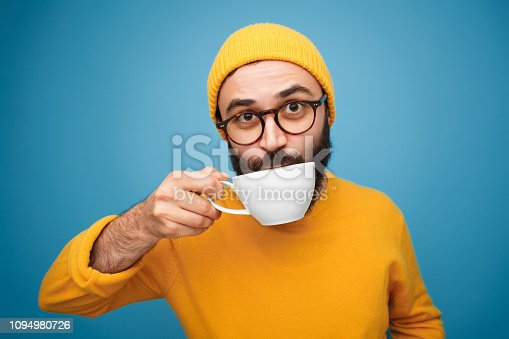 Portrait of bearded hipster in yellow drinking tea from cup looking at camera on blue.
