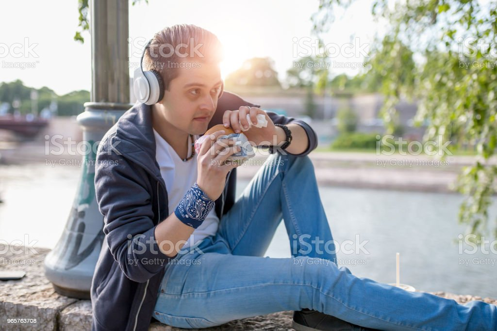 Stylish guy sits on the quay on the background of the river and the bridge. He wears blue jeans. Male looks up. Outdoors. Horizontal. - Royalty-free Adult Stock Photo
