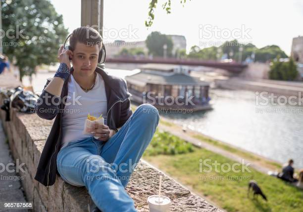 Stylish Guy Sits On The Quay On The Background Of The River And The Bridge He Wears Blue Jeans Male Looks Up Outdoors Horizontal Stock Photo - Download Image Now
