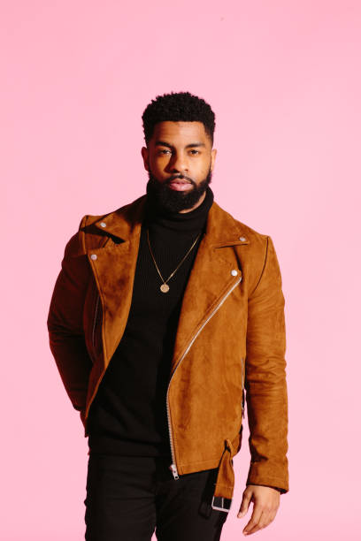 stylish, handsome and cool african american man with beard, isolated on pink studio background - carlos david stock pictures, royalty-free photos & images