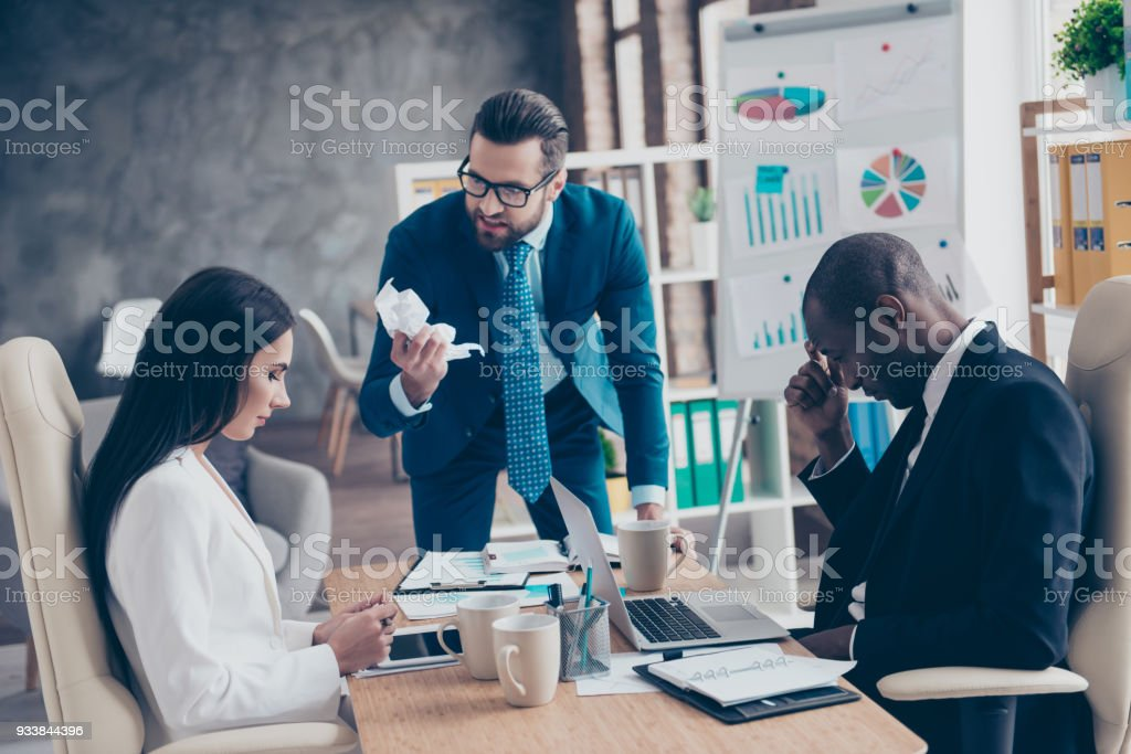 Stylish, handsome, attractive, unhappy man in glasses is out of himself because of crisis, ruin, devastation of company, holding crumpled paper in hand, standing in workstation, workplace stock photo